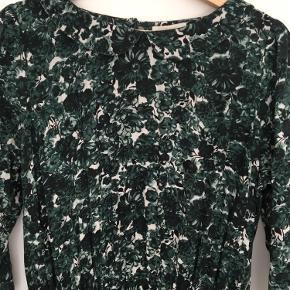 Virkelig sød kjole perfekt til vinter og efterår med de mørke natur farver.  Kjolen har trekvarte ærmer og super sød Peter pan krave.  Kjolen går ind i livet og har en flæse i livet.