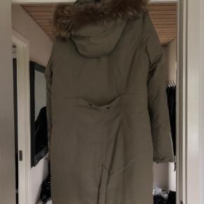 Super lækker Eskimo jakke i flot grøn farve. Ægte pels i hætten som kan lynes af. Den har som det eneste en lille prik bagpå, eller ser den ud som ny.