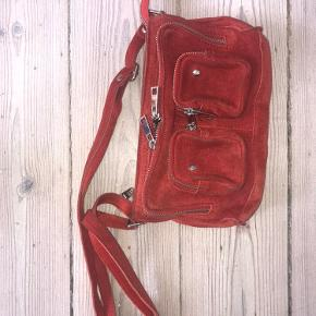 Jeg sælger denne røde nunoo x message ruskindstaske, da jeg ikke får den brugt nok. Det er en fed taske der er overraskende rummelig af sin størrelse med mange separate rum.