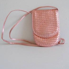 Metallisk pink vintage taske fra Bottega Veneta. Utrolig sød og sommerlig. Kan lige indeholde det essentielle.  Har været bundet op i en knude i enden af stroppen, og har derfor noget misfarvning der og problemer med at rette sig ud.  Mål: Strop: 2x50 cm Højde: 19 cm Bredde: 13 Dybde: 2 cm