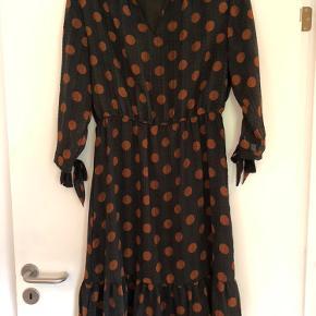 Rigtig fin kjole fra Vero Moda i mørk grå med rustfarvede cirkler.  Fin detalje med bindebånde ved ærmerne. Kjolen går til lige under knæene - jeg er 175 cm.  Kjolen er brugt tre gange, så fremstår som ny.