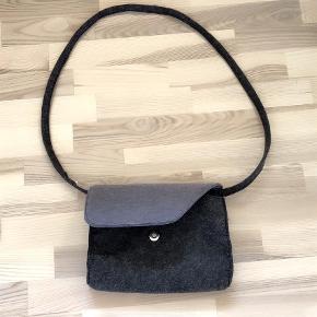 Varetype: Grå filttaske med skulderrem Størrelse: 26cm  bred 20cm høj Farve: grå  Grå filttaske med skulderrem.Tasken måler 26 cm i bredden og 20 cm i højden .