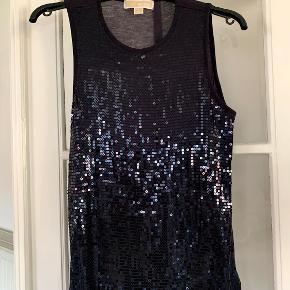 En behagelig top, som er nem til at dresse et outfit op med palietter på fronten. Toppen er 65 cm lang og 76 cm hen over brystet.
