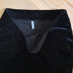 Tætsiddende nederdel i velour. Kan også passes af str S da den er med massere af stretch  92% polyester 8% Elastan