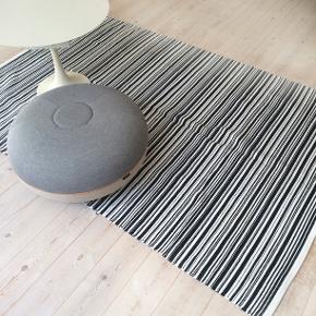 Gulvtæppe fra H Skjalm P  Det bløde tæppe er ideelt under spisebordet eller sofabordet, til et børneværelse eller sofa arrangement. Det er et kraftigt bomuldstæppe lavet af bomuldsstrimler, fra danske H Skjalm P. i et enkelt og klassisk sort-hvidt design. Kan vaskes på 30 graders vask i en alm vaskemaskin. Sælges, da vi har lidt for mange tæpper efter at have flyttet sammen. Nypris 999kr mål 125x195 cm