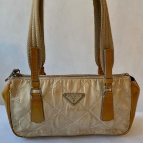 Lækker beige Prada taske i et quiltet materiale.  Super lækker farve her til foråret/sommer.  Tasken er i god vintage stand, dog har den lidt patina.