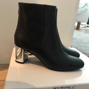 Flotte sorte læder-støvletter med sølvhæl. Aldrig brugt, stadig med prismærke og med original æske. Normal i str. Nypris var 1150,-så ca 70% rabat på nogle helt ubrugte læderstøvletter!