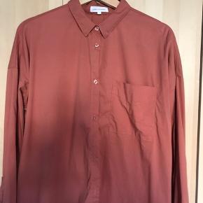 Skjorte i bomuld, nylon og spandex så den har en form for strækkvalitet. Har ingen tydelige tegn på brug. Farven er rustrød.
