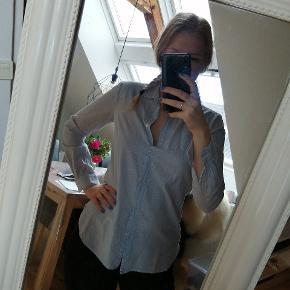Lyseblå skjorte med fine striber i stoffet.