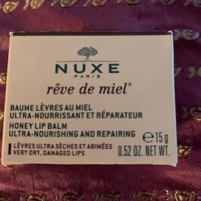 Nuxe Rêve de Miel Honey Lip Balm er en yderst nærende balm til læberne. Den er beriget med honning, botaniske olier og propolis, som er en særlig ingrediens som stammer fra en bikube. Disse ingredienser gør tilsammen at denne læbepleje er fantastisk mod tørre og sprukne læber, da den øjeblikkeligt vil berolige, nære og reparere den tynde hud på læberne. Den har en virkelig lækker konsistens, som smelter på læberne, og når man først har prøvet Nuxe Rêve de Miel Honey Lip Balm vil man slet ikke kunne undvære den igen.