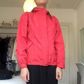 b0cba293e09 Rød regnjakke med lynlåslukning og justerbar elastik for neden. Har desuden  hætte og to lommer