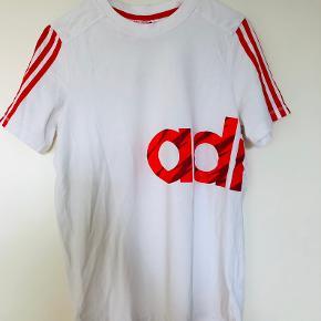 T shirt brugt en gang. Hvid med rød/ orange skrift.
