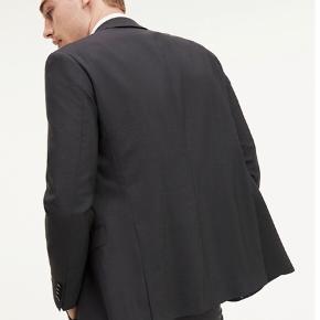 HELT NYT jakkesæt i fin uld fra Tommy Hilfiger (98% Virgin uld / 2% elestan) Pasformen er slim fit og der er utrolig god bevægelse og stræk i materialet. Aldrig brugt og stadig med mærke i. Størrelsen er 50 og farven er mørkegrå.  Kan købes i butikkerne og på nettet nu - se gerne flere billeder og beskrivelse på Tommy Hilfigers hjemmeside:  https://dk.tommy.com/slim-fit-flex-technology-blazer-tt0tt02399024  https://dk.tommy.com/slim-fit-wool-suit-trousers-tt0tt02400024  Sættet koster 3.400 kr for nyt og sælges samlet til 2.000 kr (sælges kun samlet!)  Sendes i dag - gratis fragt ☀️
