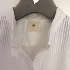 Smuk hvid skjorte i 100% bomuld fra Heartmade i st. 44 - Tjek mål: Fra under ærme til under ærme: 2 x 55 cm Talje: 2 x 50 cm - Ryggen er med indsnit. Længde fra skulder og ned: 71 cm - lidt længere midt på. Skjorten er brugt 1 gang og vasket 1 gang. Modellen er nogle år gammel men usædvanlig smuk. Den lille krave bøjes indad og hæftes med 3 knapper. Nypris kr. 1.500,00 MP 400,00 pp Bytter ikke.