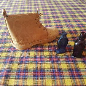 Sjov lille læderstøvle, som kan bruges enten bare til pynt eller som sparebøsse. Derudover 2 små glasflasker i brun og mørkeblå. Den blå ligner en fisk og den brune har noget meget småt skrift på sig. Begge er omkring 4 cm. Høje. Byd.