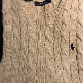 Dejlig blød og varm cable knit (kabel strik) fra amerikanske Ralph Lauren. Beige/sand-farvet blødt bomuld med broderet blåt Polo-spiller logo.  Trøjen er ikke brugt meget og derfor i rigtig flot stand. Fantastisk til den kolde danske vinter og det kølige forår.