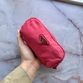 Fin lille kosmetik taske fra Prada. Den er i rigtig god stand, men den har en minimal plet fra noget gammelt make-up (se billede). Den har også en lille lomme inden i tasken med lynlås.