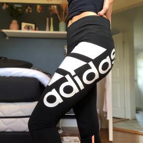 Fede træningsbukser fra Adidas med et stort logo på låret. Ingen tegn på at de er brugte. De går til lige under knæene og er en str. xs.