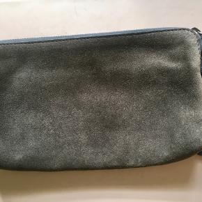 Fin stor pung / lille clutch fra Yvonne Kone . Har lidt overfladiske skrammer hist og pist (se foto), men overordnet set er den i god brugbar stand uden pletter, fnuller eller lign. Indvendig er den i perfekt stand. Har et stort rum og et lille rum. Mål: 20x13 cm. Søgeord: pung clutch mørkegrøn mørkegrå Grey ruskind suede klassisk wallet purse varm grå lynlås