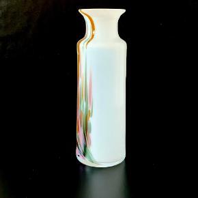 """Slank Cascade karaffel. Designet af Per Lütken for Holmegaard. Cascade blev formgivet som en reaktion på det """"perfekte"""" ensartede glas, men var for dyrt og besværligt til en stor produktion. Ses kun sjældent. Kumme blæst i opalglas med indlagte farvede flusser under overfang i krystalglas. Farver og størrelser varierer i Cascade-serien, da glasset er gennemført håndarbejde. Ikke signeret Højde: 20 cm Diameter: 7,4 cm"""