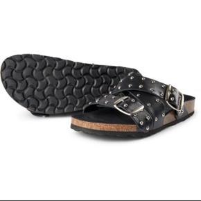 Cool sandaler fra Shoe The Bear.  Helt nye og ligger i org. æske.  Sandalerne har krydsende remme over forfoden og vristen, som er besat med sølvfarvede nitter. Sandalens sål er lavet af kork med et lag ægte læder. Snuden er desuden fodformet, og spænderne er justerbare. Perfekte til sommer sammen med en feminin kjole for en fed kontrast.