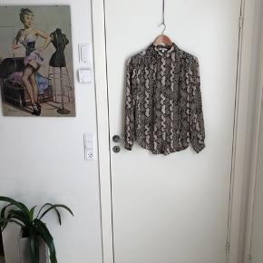 Skjorte i slangeskinds print. Brugt meget lidt. Den er løstsiddende med knaplukning.