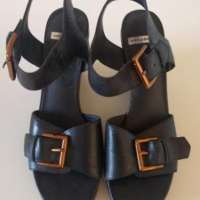 Super fine og meget smukke og elegante sandaler med kilehæl fra Vagabond, str. 38. Sandalerne er i sort læder med kobber farvede spænder. En virkelig lækker kvalitets sandel, der sidder på foden - og de har en fantastisk pasform. De har kun været på en enkelt gang og de fremstår som nye.
