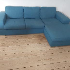 Jeg sælger min fine blå sofa med chaiselong. L: 240cm, B: 85cm og chaiselong: 150cm. Den er brugt men pæn og velholdt :) Bæres selv ned fra 1. sal ved køb!