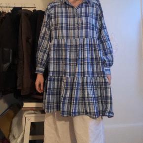 Sød country, det lille hus på prærien agtig kjole i blå ternet. Med krave og knapper ved halsen. Kan bruges både sommer og vinter. En dejlig og behagelig hverdags kjole i 100% bomuld.
