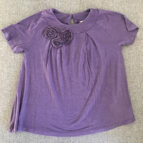 Løs t-shirt med blonde blomster ved det ene bryst.
