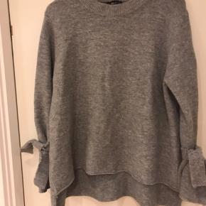 Super lækker sweater med bindedetaljer på ærmer . Tryk på køb nu!