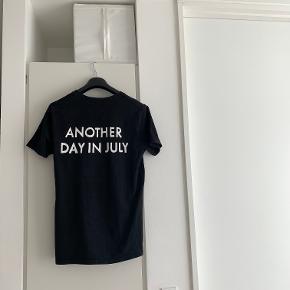 Sort t-shirt med teksten 'Another day in July' på ryggen, fra HAN København. Str. L. Brugt og vasket et par gange.  Se gerne mine andre annoncer - mængderabat gives ved køb af flere ting! Køb 4 ting og betal kun for 3 - få den billigste med gratis :-)