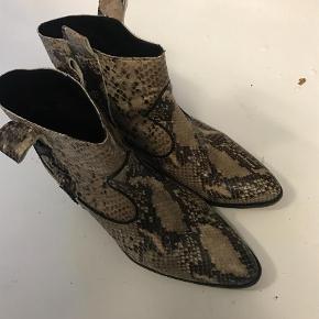 Varetype: Cowboystøvler Farve: Beige Oprindelig købspris: 1800 kr. Prisen angivet er inklusiv forsendelse.  Rigtig fine snakeskin støvler fra custommade. Kun brugt et par gange