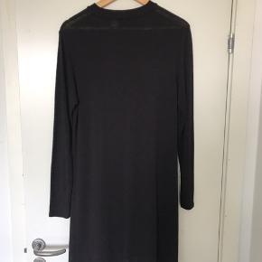 Flot, knælang kjole med høj hals og lange ærmer.