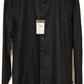 Skjorte med lidt stræk. Modellen hedder 'Fillip'. Nypris 800 kr. 100% bomuld. Brystvidde: 53 cm. X 2. Længde: 75 cm.