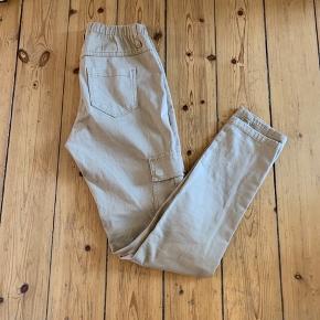 Højtaljede beige bukser med lommer på benene