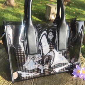 Gennemsigtig taske med tilhørende lille taske indeni. Kun brugt enkelte gange