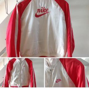 Varetype: Bomber Farve: Hvid,Pink  Cool og funky let jakke fra Nike . Perlemors hvid med strik/rib kant. Stærk pink/orange ærmer og logo. Står str large i den men jeg vurderer den lille large.