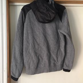 En lækker hættetrøje i grå og sort fra Nike i str M! Den er brugt få gange og derfor ingen tydelige tegn på brug.