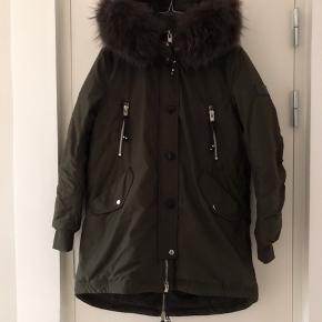 Olivengrøn jakke fra Rock'n Blue. Bemærk jakken er med AGTE pels! Style nr er, CAT.  Tags og skilt medfølger.  Nypris Kr. 3000 kr.