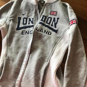 """Brand: NOZ Varetype: Striktrøje Farve: Grå Oprindelig købspris: 700 kr. Prisen angivet er inklusiv forsendelse.  Lækker lækker engelsk """" prepschool"""" / Chricket trøje, magen til den det britiske Chrickethold har på.  Str. hedder L og mærket NOZ.  Købt i London i sin tid.  I den gode ende af """"God men brugt."""" Mål: L: 53cm. B:40 cm Ærmegab: 42cm."""
