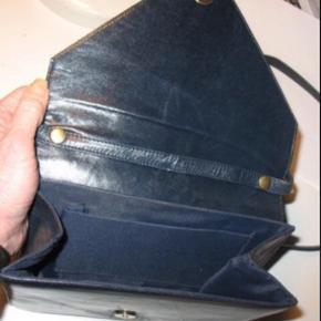 """Varetype: Clutch / Crossover Taske Håndtaske Skuldertaske fra Illums Bolighus. Størrelse: 21 x 18 cm Farve: Mørkblå / sortblå / Navy  Flot skindtaske med rem til skulder.   Remmen kan """"knappes af"""", så tasken kan anvendes som clutch / kuverttaske.   Med remmen på, kan den også benyttes som """"Cross Over"""".  Remmen er ca 105 cm lang Den er superfin - også indeni - og flot foret. Lidt """"negle ridser"""" ved lukning ellers helt perfekt og som ny. Købt i Illum / Illums Bolighus  #30dayssellout"""