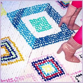 Hvidt Marokkansk Boucherouite gulvtæppe med multifarvet mønster i gulv, orange, rød, lyserød, blå og grøn, grå og sorte nuancer, og med røde frynser i den ene side. Købt i Marokko. Måler 140 cm i bredden og ca. 216 cm i længden. Skal hentes i København V.