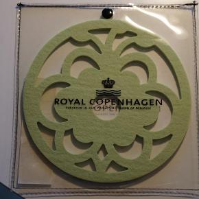 Varetype: Bordskåner Størrelse: 18x18 cm Farve: Lys Grøn  Bordskåner fra Royal Copenhagen i Lys grøn, har ikke været brugt.  Køber betaler porto og evt. Ts Gebyr  Handler gerne via Mobilpay.  Bytter ikke.