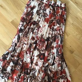 Super fin nederdel med blomstermønster i nuancerne rød, mørkebrun & Rosa. Brugt få gange, da den desværre er for stor