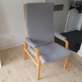 Dansk produceret lænestol med blå-gråt stofbetræk. Nogle sorte mærker nederst på benene, men ellers i rigtig god stand.   Stolen skal afhentes i Aalborg.