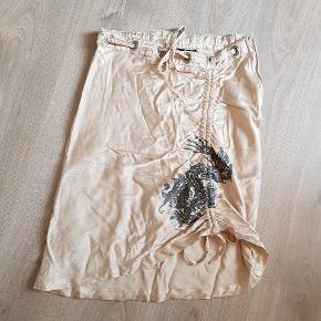 Champagne farvet nederdel. Størrelse 38, men kan også passes af 34-36, da du kan justere i taljen med båndet. Også bånd forneden så du kan have fuld længde eller en slids.   Dragemønster og små palietter.  Trænger til at blive strøget.  (retro, mini, unik)