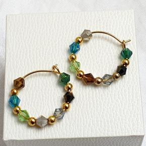 Hjemmelavede øreringe med små koniske krystaller og guldkugler, på nikkelfri guldtone hoops, diameter 2,1 cm.  Fast pris. Æske kan tilkøbes for 5 kr.  Se også mine andre annoncer med smykker 🧚♀️