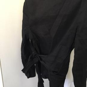 Bluse med bindebånd i taljen. Brugt 1 gang. Blusen har en smule stræk i stoffet.