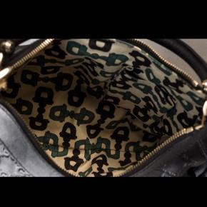 Smuk Gucci skuldertaske - sort logopræget læder m lynlås.  Opdelt i et stort rum med sidelomme til mobil samt rum m lynlås Rent interiør og ingen brugstegn Højde m hank: 36 cm. Bredde: 30  Er købt på Lauritz, dustbag medfølger  Bytter ikke
